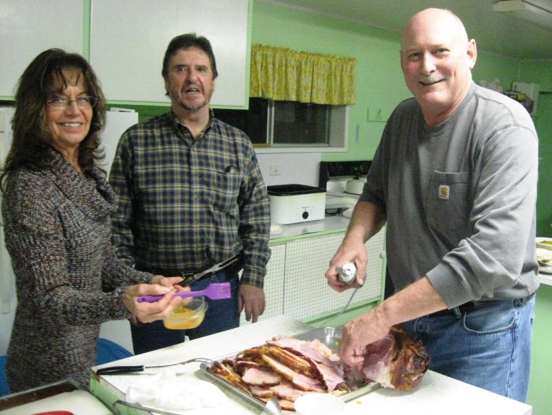 Kevin Reichert Jeanne Reichert and Peter Glover carving the potluck ham